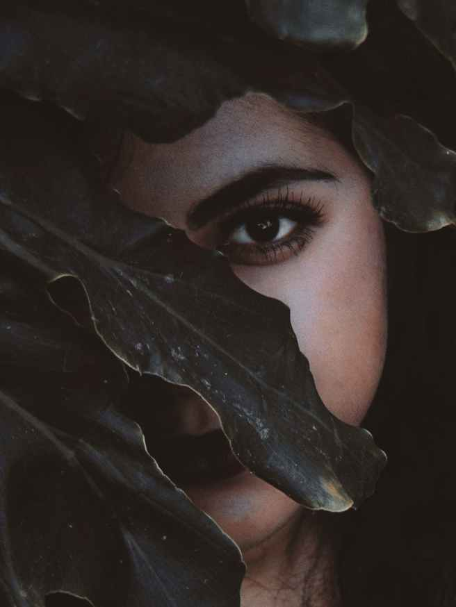woman s face behind the leaf close up photo