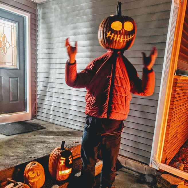 person wearing jack o lantern face disguise